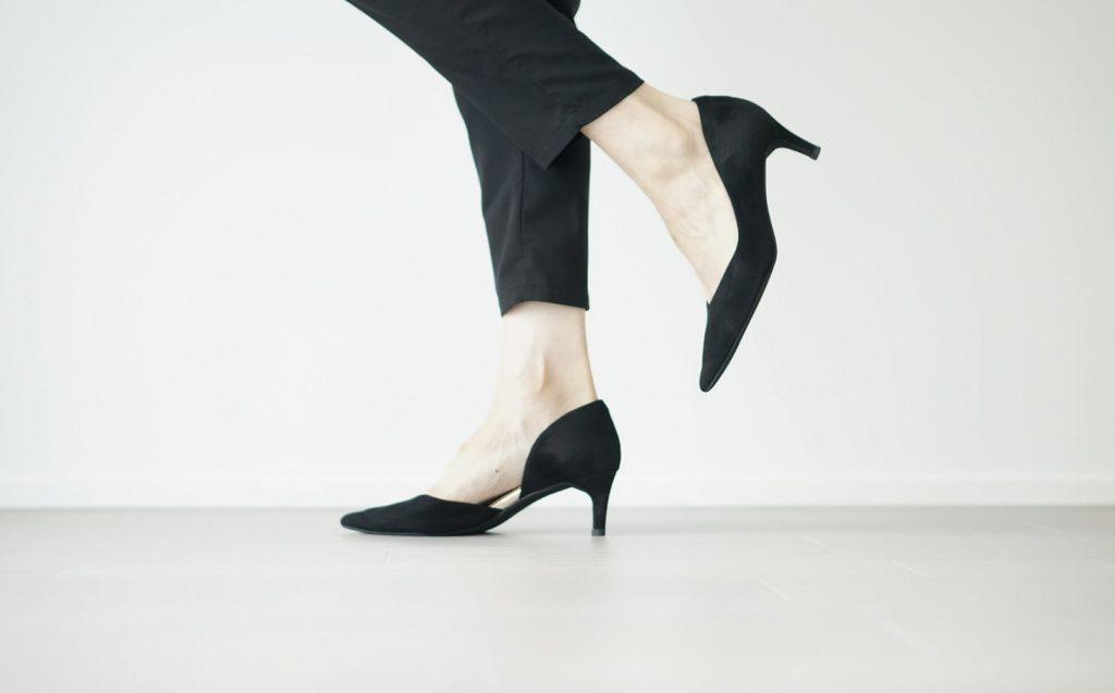 黒いパンプスをはいたパンツスーツ女性の足